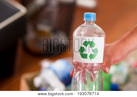 Close up of a hand holding a plastic bottle with a printed sign of recycling in front, recycle and safe the world from global warming concept.