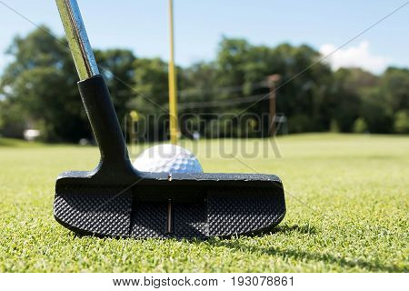 A putter is lined up behind a white golf ball with the yellow pin on the green in view