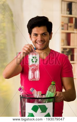 Smiling young man putting a plastic bottle inside of a small black garbage collector full of plastic, recycle and safe the world from global warming concept.