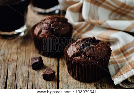 Chocolate chips oats chocolate muffins on a wood background