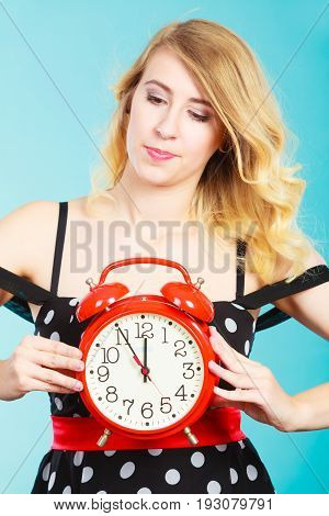 Management time concept. Blonde fashion girl wearing black dotted dress serious pensive face expression with alarm clock on blue.