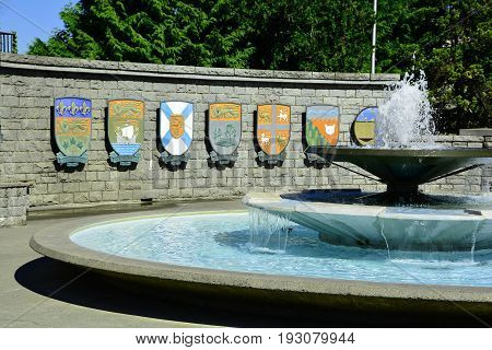 Victoria BC,Canada,July 28th 2014.A pretty setting in Victoria BC with the coats of arms of the Eastern Canadian provinces and the Northwest Territory and Nunavut with a erupting fountain in the foreground.
