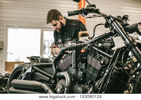 Motorcycle mechanic repairing electronics sports black bike. Handsome mechanic working in auto repair shop.