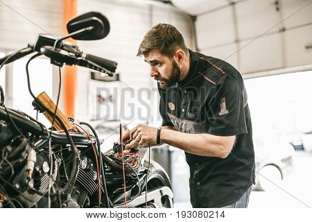 Motorcycle mechanic repairing electronics sports black bike. Handsome mechanic working in auto repair shop.