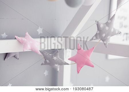 Baby bed with pinwheel garland. Pink and gray stars garland in the children's room.