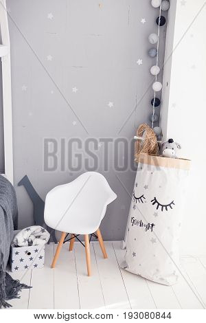 Toddler room with white cradle, chair and storage bag.