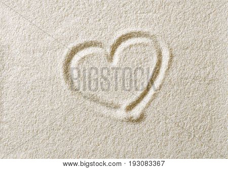 Heart symbol drawn in sand surface. Heart shape, an ideograph to express emotion like romantic love. Metaphoric. Macro photo close up from above.