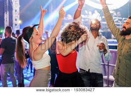 Young friends dancing in night club festival event party with dj in background - Happy people having fun inside disco - Nightlife concept - Unfiltered photo with soft focus on left girl face