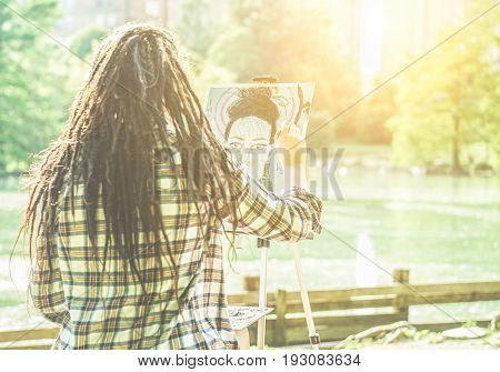Artist girl painting self-portrait in city lake park outdoor - Young painter woman with dreadlocks at work outside at sunset - Contemporary art concept - Focus on her hand - Warm contrast filter