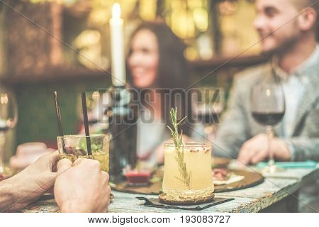 Blurred friends enjoying appetizer cocktails in speakeasy bar - Young people drinking wine and tropical fruits alcohol drinks - Friendship and social concept - Focus on rosemary - Vintage retro filter