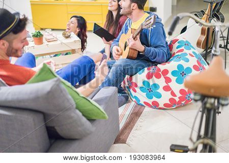 Group of trendy friends having fun in hostel living room - Happy young people enjoying time playing music and watching videos on smartphone - Focus on man left hand guitar - Warm contrast filter