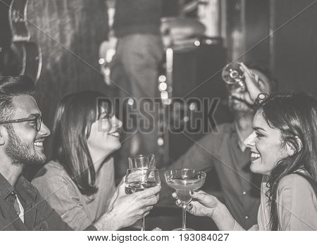 Happy friends cheering at cocktail jazz bar - Young trendy people having fun drinking alcohol and laughing - After dinner party concept - Focus on left man face - Black and white vintage editing