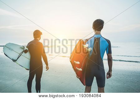 Young surfers waiting the waves on beach with sunrise in background - Sport friends looking the horizon ready for surfing - Extreme sport concept - Soft focus on right man - Warm contrast filter