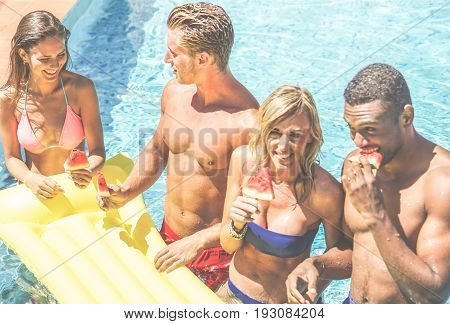 Happy friends eating watermelon in swimming pool hotel resort - Diverse culture couples having fun in summer vacation - Travel youth holidays concept - Focus on left girl - Warm cinematic filter
