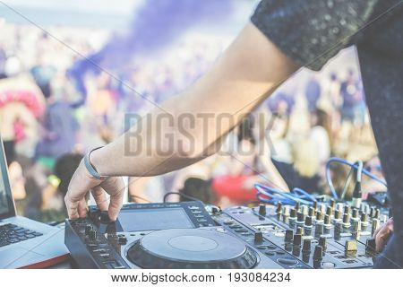 Dj mixing at disco party on the beach outdoor - Disc jockey playing music with smoke bombs colors and people dancing in background - Festival fun concept - Focus on left hand - Warm vintagefilter