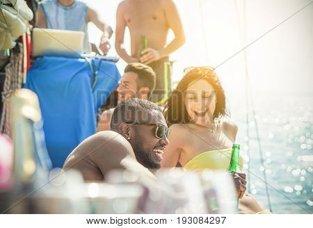 Happy young friends having exclusive boat party in caribbean sea - Diverse culture people having fun drinking beerchampagne and listening music - Focus on black man face - Rich and vacation concept