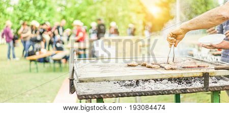 Man cooking bbq meat at festival outdoor - Chef grilling sausages in park outside - Concept of summer party with families and friends - Warm filter with back sun light - Focus on hand tongs