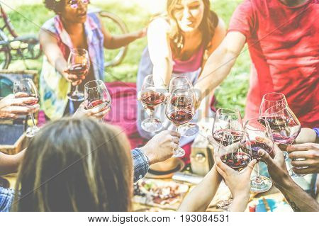 Group of friends enjoying picnic while cheering with red wine and eating snack appetizer outdoor - Young people drinking and having fun together - Focus on right bottom glasses - Vintage retro filter