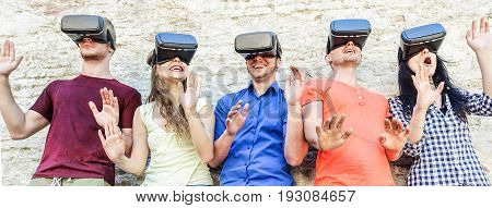 Young students wearing virtual reality glasses outdoor - Young people having fun with new technology vr headset goggles - Main focus on middle friends - New generation mania trends - Warm filter