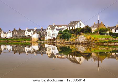 View of Port Ellen town houses with water reflection on Isle of Islay Scotland United Kingdom