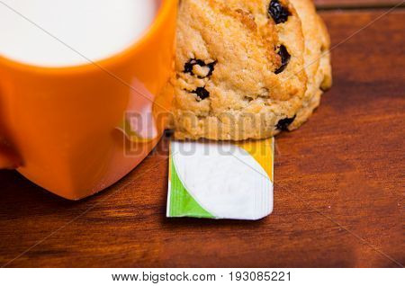 Close up of an orange glass of milk with a chocolate cookie baked with stevia, with a stevia paper bag on wooden background.
