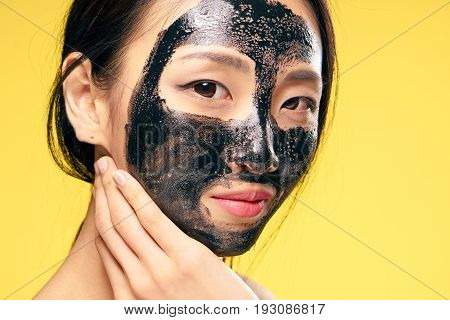 Black coal cosmetic face mask, asian, woman on yellow background.