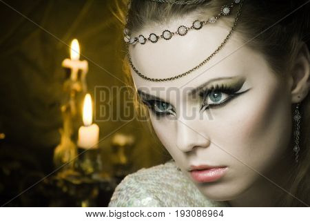 beautiful blond daring young woman with red lips big eyes and earrings. Evening make-up