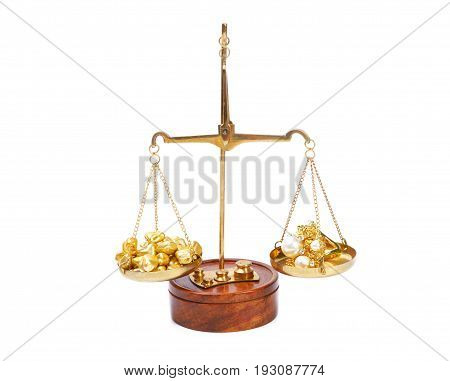 Gold and silver rocks  and golden ring with diamonds and pearls on wooden old scale