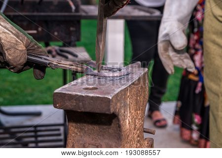Two Blacksmiths Near The Anvil. One Hacks A Horseshoe With A Hammer. In White Gloves And Robe. Horiz