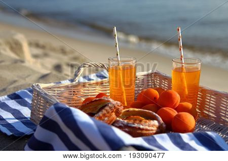 a picnic on the beach with lemonade,apricots and sweet rolls