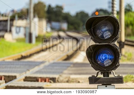Routing traffic light with a red signal on railway. Railway crossing with semaphore. Limited depth of field.