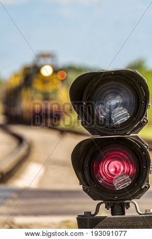 Routing traffic light with a red signal on railway. Railway semaphore signal prohibiting movement on a blurred background approaching train. Limited depth of field.