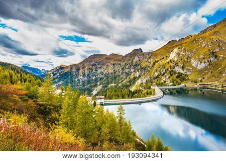 Grandiose glacial lake Lago di Fedaia in the Dolomites. Cloudy cold autumn day. The concept of ecological and extreme tourism