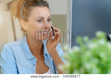 Customer service operator talking on phone in office