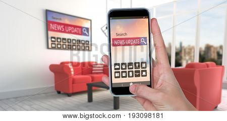 Human hand holding mobile phone against white background against red sofas in modern living room