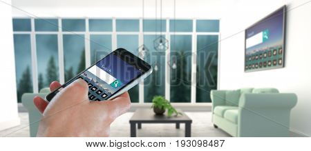 Close-up of hand holding mobile phone against blue sofas on floor in modern living room