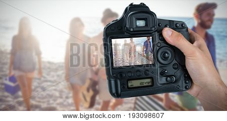 Cropped hand of photographer holding camera  against happy friends having fun together