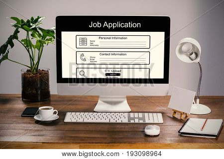 Digitally generated image of Job Application  against computer with personal organizer and belongings