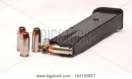 A pistol magazine loaded with several bullets with some outside of it