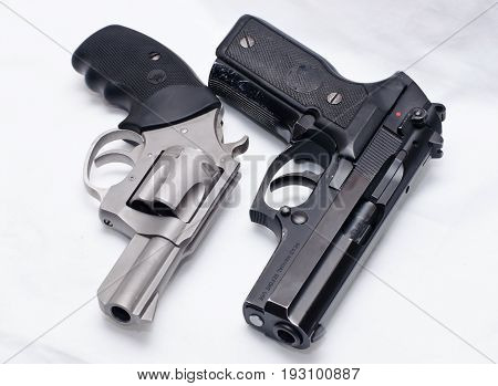 A stainless revolver placed next to a black semi automatic pistol