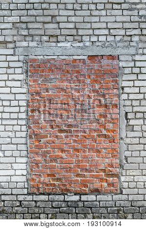 In the brick wall of white brick capped with red brick window. Masonry is uneven. There are chipped. The bottom bricks are dirty.