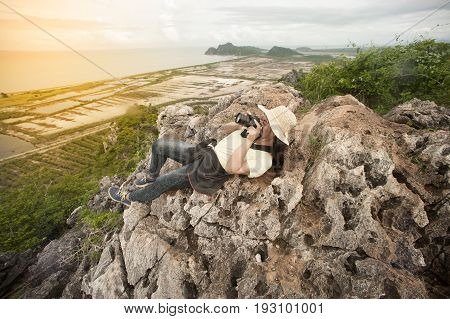Happy female lying on top of mountain is tourists view point and take a photo.