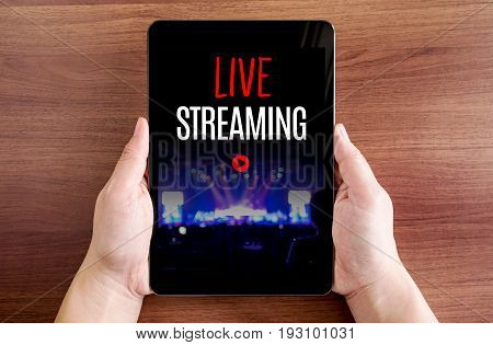 Two hand holding tablet with Live streaming and play icon on screen at dark brown table topDigital business concept.