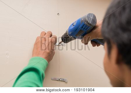 worker screwing a screw into a wall with a power drill.
