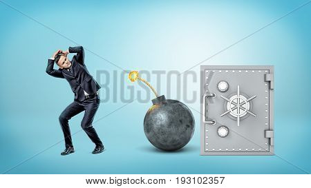 A scared businessman trying to cover himself from an iron lit bomb while standing beside a silver safe box. Bank safety. Robbery. Market bust.