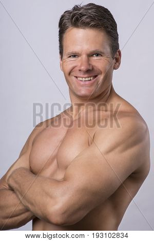 Handsome Caucasian middle-aged man in his forties smiling and posing with shirt off on light gray background