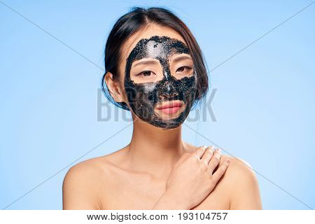Asian, woman on a blue background, black coal cosmetic face mask.
