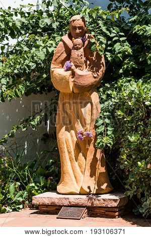 SAN DIEGO, CALIFORNIA - JUNE 24, 2017:  Statue of St. Anthony of Padua with an infant at the Mission Basilica San Diego de Alcala, the first Franciscan mission in The Californias.