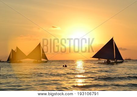 White beach, Boracay island, The Philippines - March 2016 The most fantastic sunsets on the White beach, Boracay island. There are a lot of sailboats in the sea with people who are enjoying the sunset.