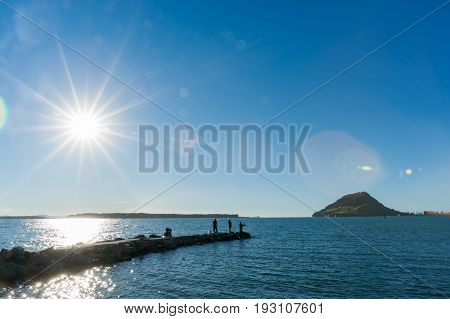 Stunning lens flare looking into sun and view Mount Maunganui on horizon over Tauranga Harbour from Sulphur Point with small silhouettes of people fishing on end of rock groin.